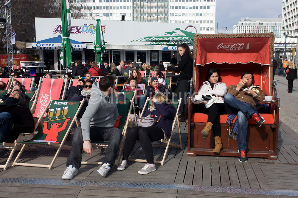 Young Germans enjoy spring sunshine on deckchairs and beach-style seating, in Alexanderplatz, Berlin Mitte. It is a warm spring Sunday after noon and many have come here to shop and sample typical German wursts and burgers, beer and sweets. Alexanderplatz is a large public square and transport hub in the central Mitte district of Berlin, near the Fernsehturm. Berliners often call it simply Alex, referring to a larger neighbourhood stretching from Mollstraße in the northeast to Spandauer Straße and the City Hall in the southwest.