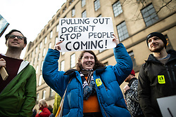 © Licensed to London News Pictures. 26/01/2019. Manchester, UK. A woman holds up a placard reading PULLING OUT DOESN'T STOP PEOPLE COMING . A cross party demonstration by hundreds of supporters of a People's Vote on Britain's membership of the EU is held in St Peters Square , followed by a march to the Mechanics Institute and rally of supporters . Photo credit: Joel Goodman/LNP