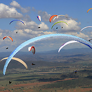 149 of the World's best paragliding pilots from 39 nations descended on the small country town of Manilla near Tamworth in northern New South Wales, Australia to contest the 10th FAI Paragliding World Championships during March 2007. The drought stricken area is renowned for it's great cross country flying from the Mount Borah hillside and over two hectic weeks, numerous incidents and mixed weather, the pilots were able to fly five tasks to decide the winners in what proved to be an extremely close contest.. The Men's competition was won by Great British pilot Bruce Goldsmith with Jean-Marc Caron of France finishing second just seventeen points behind with Thomas Mccune of USA finishing third. The women's competition was won by Petra Slivova of Czech Republic with Viv Williams of Australian just fifteen points behind and New Zealand pilot Harmony Gaw finishing third. .In the team event Czech Republic finished first followed by France and Switzerland...Pilots take to the skies during competition where they form gaggle's and look for the best lift from thermal's...
