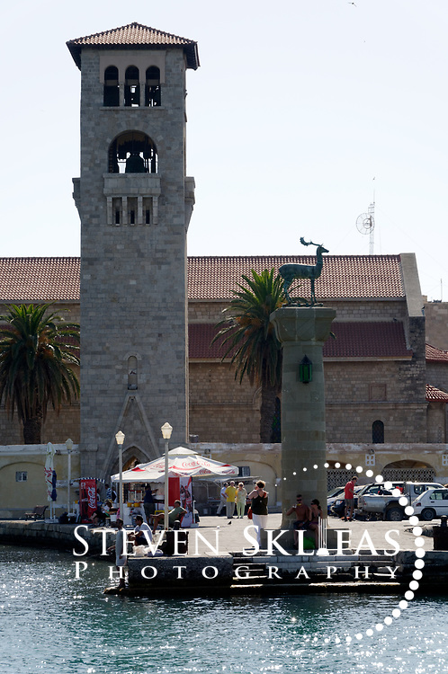 Rhodes. Greece. Evangelismos church tower and deer statue column standing on the historical spot of the Colossus of Rhodes. Two bronze statues (one depicting a stag and the other a doe) stand on columns guarding the Mandaraki harbour entrance where the bronze 35 metre (over 100-feet) Colossus of Rhodes was believed to have stood. Built in 305 BC, the Colossus was one of the Seven Wonders of the Ancient World and depicted the sun god, Helios holding a flaming torch. A violent earthquake in 227 BC caused it to topple over. The island of Rhodes is the largest of the Dodecanese Island group and one of the most popular Greek Islands.