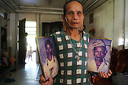 Lun with pictures of herself and her deceased husband. We had walked to the blockades together twenty years ago. Sungai Asap Longhouse community where Long Geng Kenyah community was forcibly resettled after their homes where flooded by the Bakun Dam. Home of the Kenyah native people who once lived in Long Geng, which was flooded by the Bakun Dam. Their community is now dispersed between Sungai Asap, Long Lewan and floating longhouses on the Bakun reservoir. Bakun Belaga region, Sarawak Borneo 2012..Borneo native peoples and their rainforest habitat revisited two decades later: 1989/1991-2012. ..The Bakun hydro-electric dam, which covers 700km². Construction of the dam required the relocation of more than 9,000 native residents, mainly Kayan and Kenyah indigenous peoples who lived in the flooded area. Many Sarawak natives have been relocated to a longhouse settlement named Sungai Asap in Bakun. Most of them were subsistence farmers. Each family were promised only 3 acres of land, insufficient to survive, and many families still have not been compensated for the loss of their longhouses..Sarawak's primary rainforests have been systematically logged over decades, threatening the sustainable lifestyle of its indigenous peoples who relied on nomadic hunter-gathering and rotational slash & burn cultivation of small areas of forest to survive. Now only a few areas of pristine rainforest remain; for the Dayaks and Penan this spells disaster, a rapidly disappearing way of life, forced re-settlement, many becoming wage-slaves. Large and medium size tree trunks have been sawn down and dragged out by bulldozers, leaving destruction in their midst, and for the most part a primary rainforest ecosystem beyond repair. Nowadays palm oil plantations and hydro-electric dam projects cover hundreds of thousands of hectares of what was the world's oldest rainforest ecosystem which had some of the highest rates of flora and fauna endemism, species found there and nowhere else on Earth, an