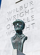 "Wilbur Wright bronze bust.  Wright Brothers National Memorial (or Kill Devil Hill Monument from 1927 to 1933), located in Kill Devil Hills, in Dare County, North Carolina, USA, commemorates the first successful, sustained, powered flights in a heavier-than-air machine. The memorial tower, built in 1932, was designed by Rodgers and Poor, a New York architectural firm. From 1900 to 1903, Orville Wright (born August 19, 1871 - died January 30, 1948) and Wilbur Wright (April 16, 1867 - May 30, 1912) came here from Dayton, Ohio, attracted to the area's steady winds and privacy. The town of Kitty Hawk (established in the early 1700s as Chickahawk) was made famous on December 17, 1903, when the Wright brothers made the first controlled, powered airplane flights six kilometers (4 miles) away near the sand dunes known as Jockey's Ridge.  In the two years afterward, the brothers developed their flying machine into the first practical fixed-wing aircraft. Although not the first to build and fly experimental aircraft, the Wright brothers were the first to invent aircraft controls that made fixed wing flight possible. The brothers' fundamental breakthrough was their invention of ""three axis-control"", which enabled the pilot to steer the aircraft effectively and to maintain its equilibrium, a method which became standard on modern fixed wing aircraft."