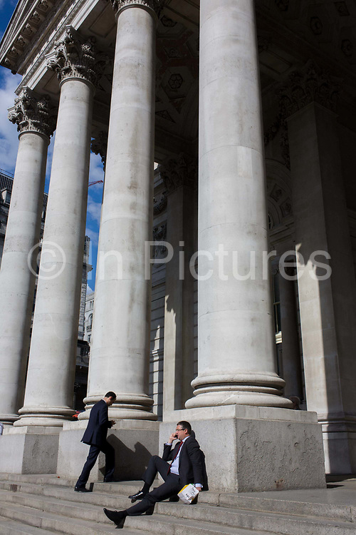 Businessmen beneath Cornhill pillars in the City of London. As a gentleman sits on the steps talking intoi a smartphone, another suit walks up beneath the tall columns of this architecture in the Square Mile, the oldest and financial heart of the capital. The classic neo-Romanesque architecture of the Royal Exchange building has Doric and Ionic columns with their ornate stonework, designed by Sir William Tite in 1842-1844 and opened in 1844 by Queen Victoria). It's the third building of the kind erected on the same site. The first Exchange erected in 1564-70 by sir Thomas Gresham but was destroyed in the great fire of 1666. It's successor, by Jarman, was also burned down in 1838. The present building is grade 1 listed and cost about £150,000.