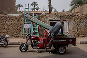 A local man loads planks onto his trike motorcycle outside a DIY shop in Luxor, Nile Valley, Egypt.