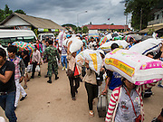 16 JUNE 2014 - ARANYAPRATHET, THAILAND: Cambodian migrant workers fleeing Thailand walk through Aranyaprathet, Thailand before being returned to Cambodia. More than 150,000 Cambodian migrant workers and their families have left Thailand since June 12. The exodus started when rumors circulated in the Cambodian migrant community that the Thai junta was going to crack down on undocumented workers. About 40,000 Cambodians were expected to return to Cambodia today. The mass exodus has stressed resources on both sides of the Thai/Cambodian border. The Cambodian town of Poipet has been over run with returning migrants. On the Thai side, in Aranyaprathet, the bus and train station has been flooded with Cambodians taking all of their possessions back to Cambodia. PHOTO BY JACK KURTZ