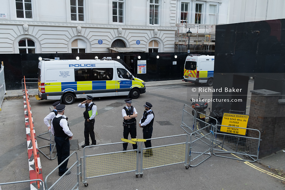 British Met Police officers stand by security gates at one of the entrances to Princes Gate, Kensington, where the Iranian embassy is located, on 26th August 2020, in London, England.