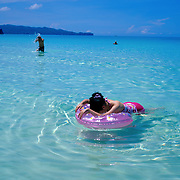 Asian tourists relaxing in the ocean at White Beach, Boracay Island, the Philippines on October 7, 2008, Photo Tim Clayton..Asian tourists at White Beach, Boracay Island, the Philippines...The 4 km stretch of White beach on Boracay Island, the Philippines has been honoured as the best leisure destination in Asia beating popular destinations such as Bali in Indonesia and Sanya in China in a recent survey conducted by an International Travel Magazine with 2.2 million viewers taking part in the online poll...Last year, close to 600,000 visitors visited Boracay with South Korea providing 128,909 visitors followed by Japan, 35,294, USA, 13,362 and China 12,720...A popular destination for South Korean divers and honeymooners, Boracay is now attracting crowds of tourists from mainland China who are arriving in ever increasing numbers. In Asia, China has already overtaken Japan to become the largest source of outland travelers...Boracay's main attraction is 4 km of pristine powder fine white sand and the crystal clear azure water making it a popular destination for Scuba diving with nearly 20 dive centers along White beach. The stretch of shady palm trees separate the beach from the line of hotels, restaurants, bars and cafes. It's pulsating nightlife with the friendly locals make it increasingly popular with the asian tourists...The Boracay sailing boats provide endless tourist entertainment, particularly during the amazing sunsets when the silhouetted sails provide picture postcard scenes along the shoreline...Boracay Island is situated an hours flight from Manila and it's close proximity to South Korea, China, Taiwan and Japan means it is a growing destination for Asian tourists... By 2010, the island of Boracay expects to have 1,000,000 visitors.