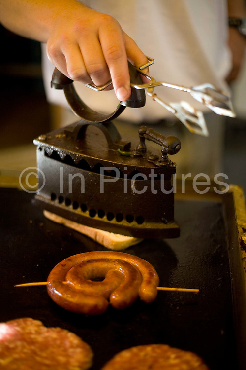 A chef irons a piece of fried bread on a griddle with a sausage at a food stall, Pec, Hungary.Pecs has been chosen as the 2010 European City of Culture. The city is on the southern slopes of the Mecsek Hills and has a sub-Mediterranean climate. Settled by Romans as Sopianae, it was a significant Christian settlement. Later conquered by the Ottomans, it has important Turkish architecture.