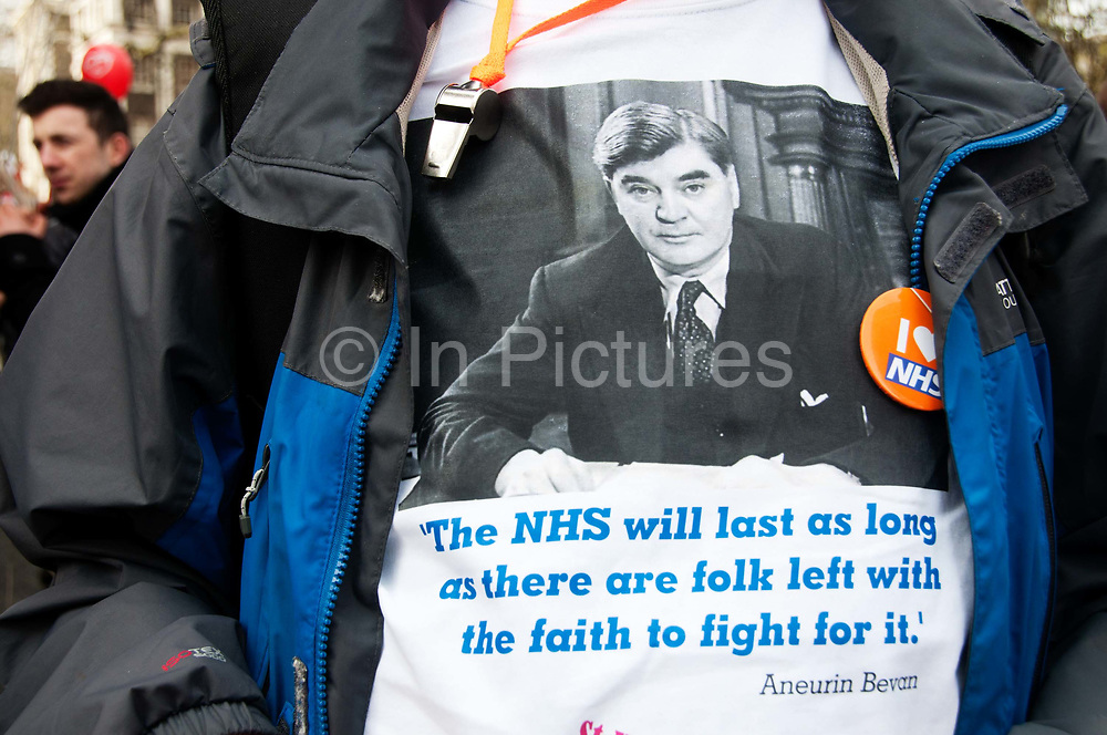 Tens of thousands of health workers, activists and members of the public protested against austerity and cuts in the NHS National Health Service on March 4th 2017 in London, United Kingdom. A trade unionist wears a t shirt showing a photo of Aneurin Bevan, who set up the NHS in 1948 with a quote from him saying The NHS will last as long as there are folk left with the faith to fight for it.