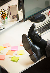 Low section of a businessman feet up on desk in an office, Bavaria, Germany
