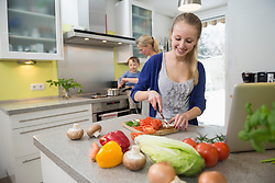 Daughter cutting vegetables while mother with son in background
