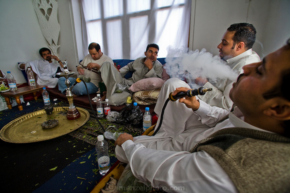 Yemeni men relax at a qat chewing session in a private home in Sanaa, Yemen. They also smoke tobacco in a hookah, eat sweets, and drink water while they chew and talk for hours.