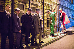 © Licensed to London News Pictures . 26/12/2017. Wigan, UK. Two men urinate against a wall as four others, dressed up as Peaky Blinders characters, pose. Revellers in Wigan enjoy Boxing Day drinks and clubbing in Wigan Wallgate . In recent years a tradition has been established in which people go out wearing fancy-dress costumes on Boxing Day night . Photo credit: Joel Goodman/LNP