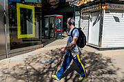 A Londoner wearing a yellow stripe on his legs, walks past the Disney shop in Oxford Street, where the yellow border frame for National Geographic is in one window, on 29th March 2021, in London, England.