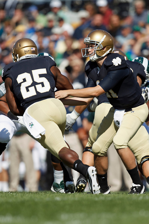 Notre Dame quarterback Tommy Rees (#11) hands the ball off to tailback Jonas Gray (#25) in action during NCAA football game between Notre Dame and Michigan State.  The Notre Dame Fighting Irish defeated the Michigan State Spartans 31-13 in game at Notre Dame Stadium in South Bend, Indiana.