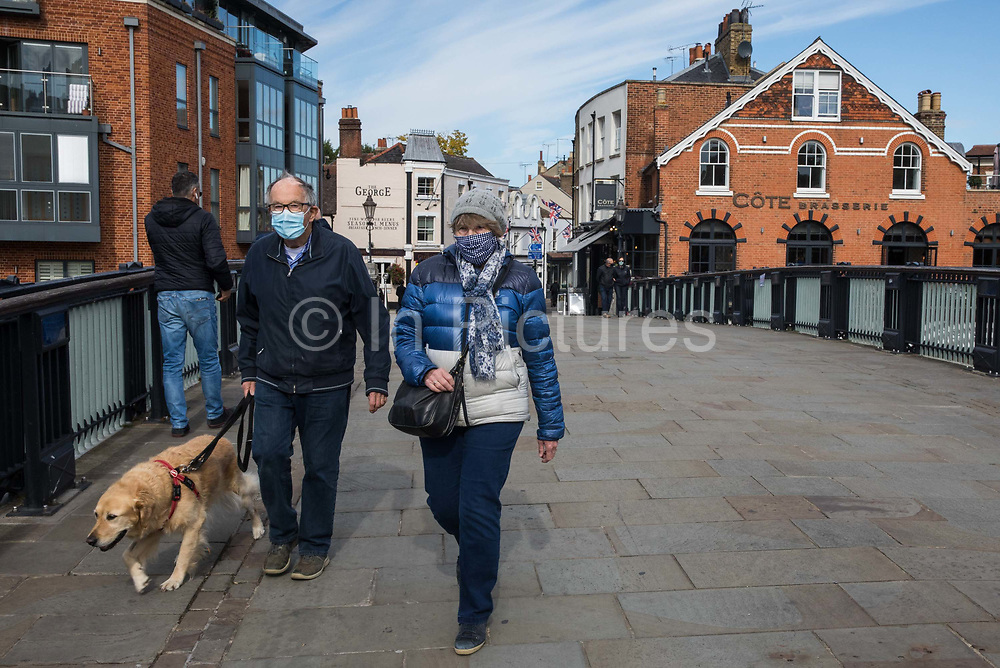 A man and a woman wearing face coverings to help prevent the spread of the coronavirus cross Eton Bridge on 26 September 2020 in Windsor, United Kingdom. The Royal Borough of Windsor and Maidenhead is aware of a rise in local coronavirus infections, has a COVID-19 outbreak management plan in place to try to ensure that the numbers do not increase further and has requested access to more coronavirus testing sites with this in mind.