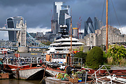 With heritage barges and 'lighters' in the foreground, the superyacht Kismet dominates the river Thames, on 20th October 2021, in London, England. 'Kismet' is a 95.2m (312 ft)-long superyacht which was built in 2014. It is managed by the Moran Yacht & Ship chartering business, and is owned by Pakistani-American billionaire Shahid Khan. Tower Bridge Moorings is the capital's only floating gardens - a sustainable way of living for a community of more than one hundred adults and children, and a shelter for wildlife on the river. Tower Bridge Moorings is the capital's only floating gardens - a sustainable way of living for a community of more than one hundred adults and children, and a shelter for wildlife on the river.