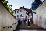 "A woman is taking a photograph with her smart phone while  walking down from Prague Castle via the Old Castle Stairs (Stare zamecke schody) down to the center of  ""Lesser Town"" (Mala Strana)."