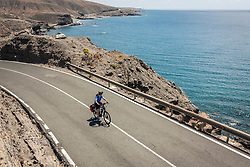 Mountain biker riding electric bicycle on road by sea