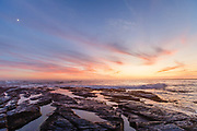 Sunset reflects in the tidal pools of the rocky shore, Newport RI