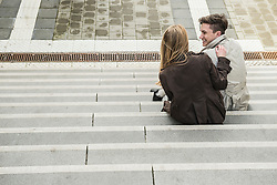 Rear view of a young couple sitting on stairs and smiling, Munich, Bavaria, Germany