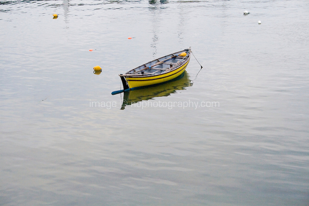 Yellow wooden rowing boat moored in Dun Laoghaire harbour in Dublin Ireland