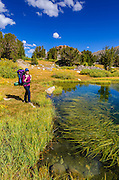 Backpacker and tarn on the Bishop Pass Trail, John Muir Wilderness, Sierra Nevada Mountains, California USA
