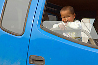 China, Beijing, Chaoyang, San Jian Fang, 2008. A child watches the action from the safety of a transport vehicle's cab. Young children can often be seen near low-tech construction zones such as these demolitions.