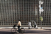 A Japanese man rides a bicycle past a delivery scooter in a sunlit street in Ginza, Tokyo, Japan. Friday December 18th 2015