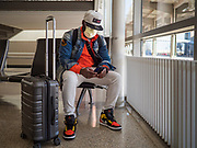 """17 MARCH 2020 - DES MOINES, IOWA:  PATRICK AWO, from Des Moines, waits for a ride home after flying into Des Moines International Airport Tuesday. The airport was almost empty as air travel is greatly reduced because of the Coronavirus outbreak. Sunday night, the Governor of Iowa announced that the state health department had recorded """"community spread"""" in Des Moines. Tuesday, the Governor ordered all restaurants and bars to close or transition to take out only. The Iowa Department of Public Health has urged all public buildings, like libraries and schools, to close, and all schools in Iowa are closed for at least 30 days.     PHOTO BY JACK KURTZ"""