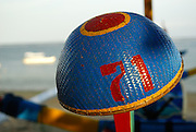 Woven boatsman's hat, with spars of traditional Jukung outrigger (sometimes called a prahu) in background. Sanur, Bali, Indonesia.