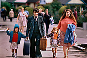 A young family anongst the thousands of arrivals for the Saturday turnaround in Butlins holiday camp, Skegness. Butlins Skegness is a holiday camp located in Ingoldmells near Skegness in Lincolnshire. Sir William Butlin conceived of its creation based on his experiences at a Canadian summer camp in his youth and by observation of the actions of other holiday accommodation providers, both in seaside resort lodging houses and in earlier smaller holiday campsThe camp began opened in 1936, when it quickly proved to be a success with a need for expansion. The camp included dining and recreation facilities, such as dance halls and sports fields. Over the past 75 years the camp has seen continuous use and development, in the mid-1980s and again in the late 1990s being subject to substantial investment and redevelopment. In the late 1990s the site was re-branded as a holiday resort, and remains open today as one of three remaining Butlins resorts.