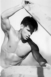 sexy shirtless man looking under a car hood