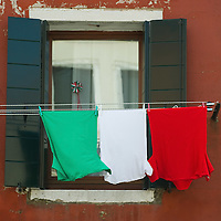 VENICE, ITALY - MARCH 17: An  Italian National Flag composed by three T Shirts hang outside a window on the day of the celebrations for the 150th anniversary of Italy's unification on March 17, 2011 in Venice, Italy. Events in various Italian cities will celebrate the 150th anniversary of Italy's unification until the end of the year. National Festivity begins on March 17.