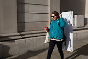 A lady carrying a white panel on her back adjusts her pony tail while walking past the Bank of England on Threadneedle Street in the City of London, the capital's financial district, carrying a travelling billboard, on 11th March 2020, in London, England.