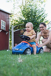 Baby boy riding on toy car with his mother pushing it from behind, Munich, Bavaria, Germany