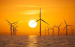 © Licensed to London News Pictures. 09/03/2018. Irish Sea, UK.  The glowing sun rising over offshore wind turbines in the Irish Sea this morning, 9th March 2018. The North West of England is set to experience clear and sunny weather. Photo credit: Rob Arnold/LNP