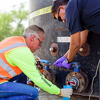 081915       Cable Hoover<br /> <br /> Navajo Nation police investigator Algernon Tsosie opens the tap so that John Isham of the environmental consulting firm Iina' Ba' can take a sample from a reportedly contaminated tank in Shiprock Wednesday.