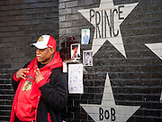 "22 APRIL 2016 - MINNEAPOLIS, MN: A man at a memorial to Prince in front of 1st Ave in Minneapolis. Thousands of people came to 1st Ave in Minneapolis Friday to mourn the death of Prince, whose full name is Prince Rogers Nelson. 1st Ave is the nightclub the musical icon made famous in his semi autobiographical movie ""Purple Rain."" Prince, 57 years old, died Thursday, April 21, 2016, at Paisley Park, his home, office and recording complex in Chanhassen, MN.    PHOTO BY JACK KURTZ"
