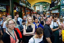 © Licensed to London News Pictures. 14/06/2017. London, UK. Traders and shoppers wait for one minutes silence to be observed in Borough Market, London as it reopens on 14 June 2017, following a terror attack that killed 8 people over a week ago. Photo credit: Tolga Akmen/LNP