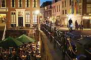 Mensen eten aan de Oudegracht in Utrecht bij het Oude Pothuys. Over de brug wordt gefietst.<br />