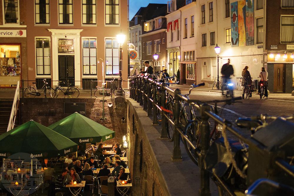 Mensen eten aan de Oudegracht in Utrecht bij het Oude Pothuys. Over de brug wordt gefietst.<br /> <br /> People are eating outside cafe Het Oude Pothuys at the Oudegracht in Utrecht. Over the bridge cyclists are passing by.