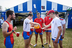 © Licensed to London News Pictures. 04/07/2018. Henley-on-Thames, UK. Rowers from Wallingford Rowing Club enjoy a post race drink while wearing England Football team shirts on day one of the Henley Royal Regatta, set on the River Thames by the town of Henley-on-Thames in England. Established in 1839, the five day international rowing event, raced over a course of 2,112 meters (1 mile 550 yards), is considered an important part of the English social season. Photo credit: Ben Cawthra/LNP