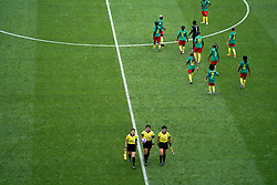 Cameroon players stay on the pitch at the beginning of half-time as match refere Qin Liang (bottom centre) walks off during the FIFA Women's World Cup, round of Sixteen match at State du Hainaut, Valenciennes.