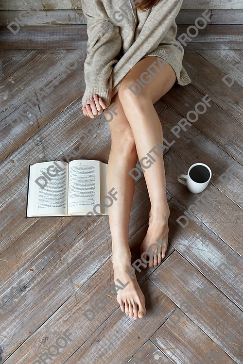 Concept of a Lazy day with a  young woman wearing a sweater sitting on wooden floor with an open book and coffee mug, barefoot top and above view