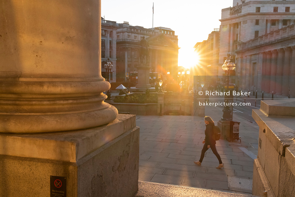 A commuter passes through evening sunlight which illuminates the Bank Triangle junction during a much quieter evening rush-hour during the third lockdown of the Coronavirus pandemic. Financial institutions and the Bank of England are located here, in the heart of the City of London, aka Square Mile, on 26th February 2021, in London, England.