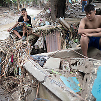 Antonio sits with his brother where their house used to be in El Calan, Honduras. Following the double hurricanes of Eta and Iota, many houses were washed away or damaged in the north, centre and west of Honduras.