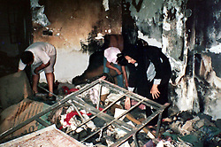 Photograph of Amira Khalid, 44, wife of Salah Izat, 51, as she tries to recover items from their  home, which burnt down last year, Baghdad, Iraq, March 2, 2004. Salah Izat's home was destroyed in March 2003 when an American missile hit just outside their front door. A year later, Izat is getting better pay wages, but has lost his right leg from diabetes. He says the lack of medical resources after the war made him unable to get proper attention for his ailing leg, possibly being the reason it became so gangrenous that it had to be amputated.
