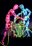 Glowing mannequins using glowing string to tie down a large hand.Black light