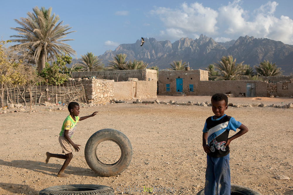 Boys playing in the streets of Hadibu, with a view to the Hagier Mountains. Socotra, Yemen